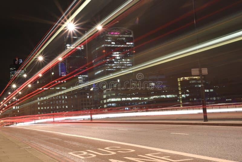 Stads- stadsnattskott på den London bron, röd buss i rörelse, långt exponeringsskott arkivbild