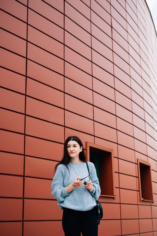 Stads- stilbegrepp Stående av den trendiga tonårs- flickan med solglasögon i hennes händer som poserar på stadsgatan i sommar gla arkivbilder
