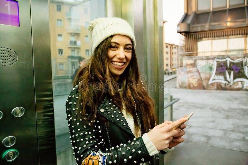 Stads- ung kvinna som använder telefonen på hissen fotografering för bildbyråer
