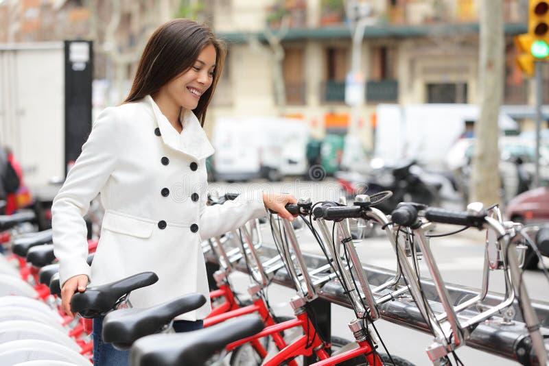 Stadsfiets - vrouw die openbare stadsfietsen met behulp van stock afbeelding