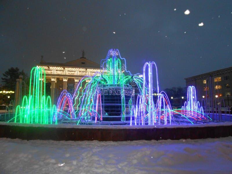 Stadsfontein op vierkant theater en sneeuw aan avondhemel stock afbeelding
