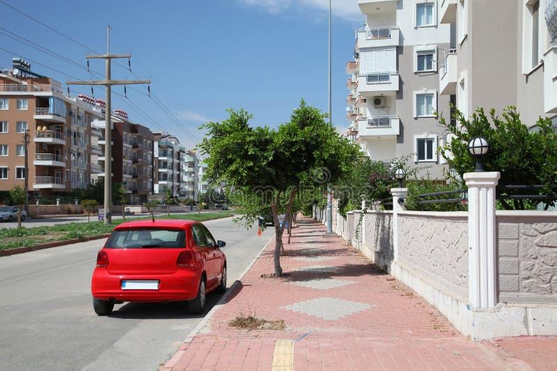 Stadsgata med den parkerade röda bilen i den soliga sommardagen royaltyfri fotografi