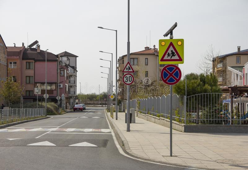 Stadsgata med en övergångsställe, en hastighetsbula och ett varningstecken 'barn 'nära ett härligt dagis royaltyfria bilder