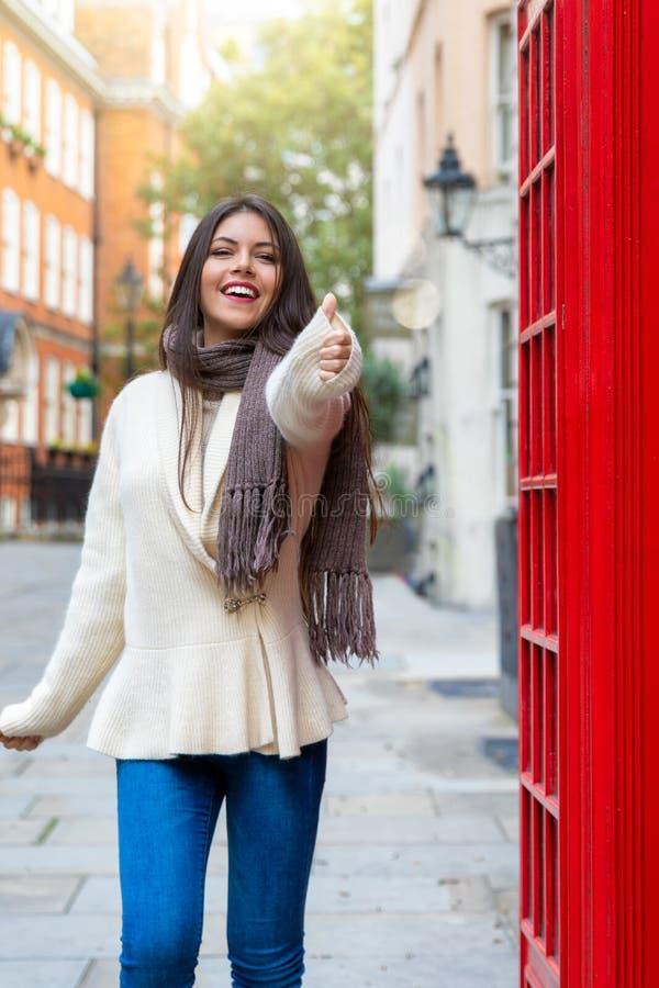 Stadshandelsresandekvinnan visar tummarna upp tecknet in London royaltyfria bilder