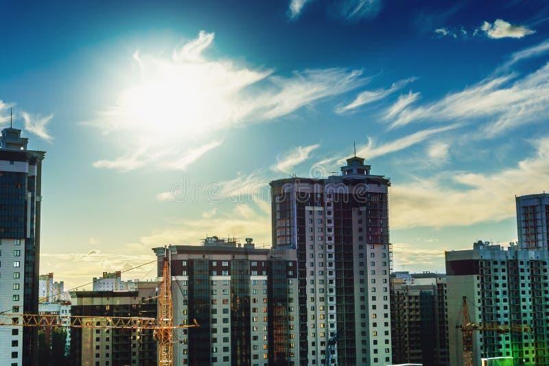 Stadshorisont, nya stora hus mot solen och blå himmel, stads- horisont, byggande yttersida, torn av kontoret och hyreshusar royaltyfria foton