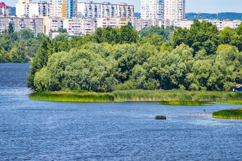 Stadshorizon over de rivier tegen de blauwe hemel stock foto