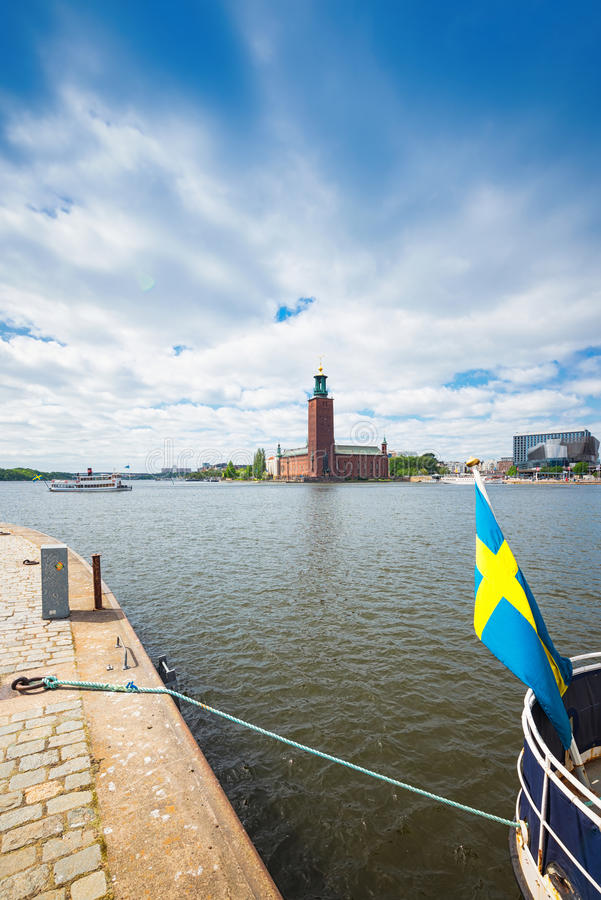 Stadshuset med förbigå för en ångbåt och en svensk flagga i royaltyfri fotografi