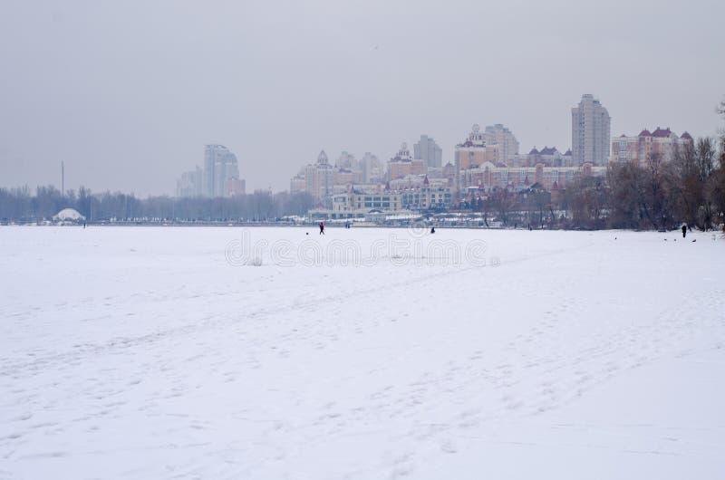 Stadsinvallning under snön, iskall flod royaltyfri bild