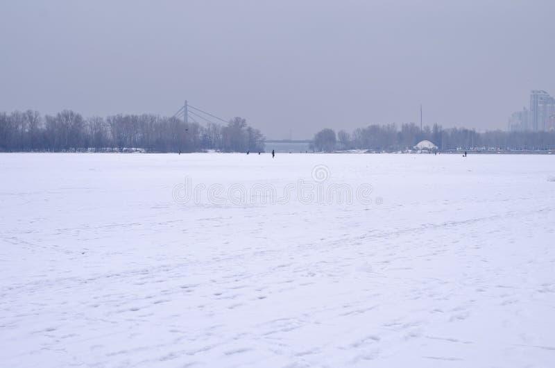 Stadsinvallning under snön, iskall flod royaltyfri fotografi