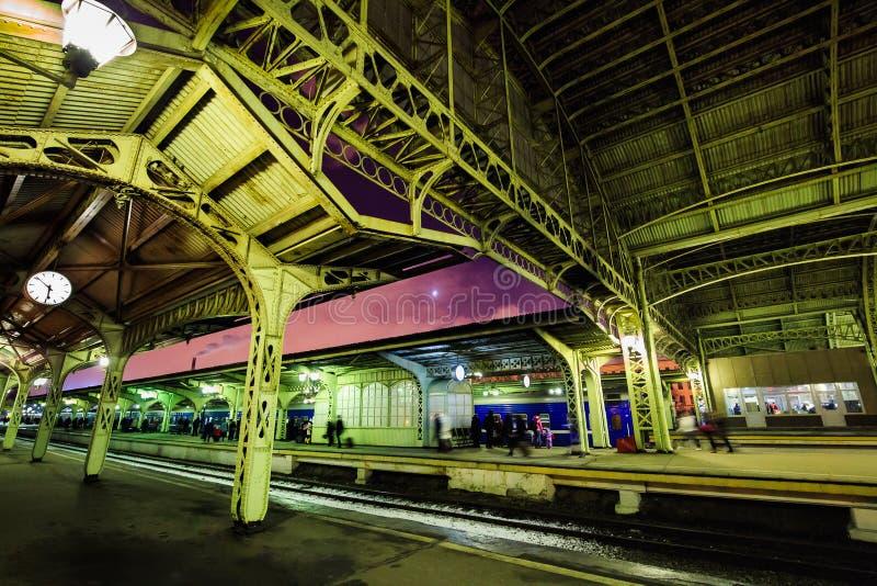 Stadsjärnvägsstation och passagerareplattform på natten i St Petersburg, Ryssland Strukturera och taket av drevstationen på skymn arkivbilder