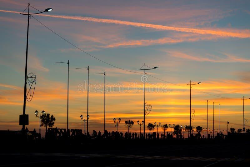 Download Stadskade Met Lantaarns, Bomen En Mensen Backlit Tegen De Heldere Zonsonderganghemel Stock Afbeelding - Afbeelding bestaande uit landschap, dijk: 107700957