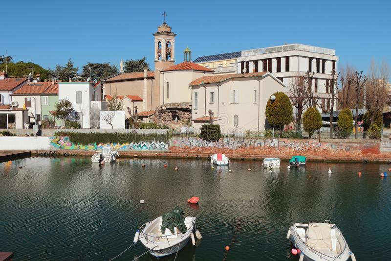 Stadskanal och Roman Catholic Church ashore San Giuliano, Rimini, Italien royaltyfri foto