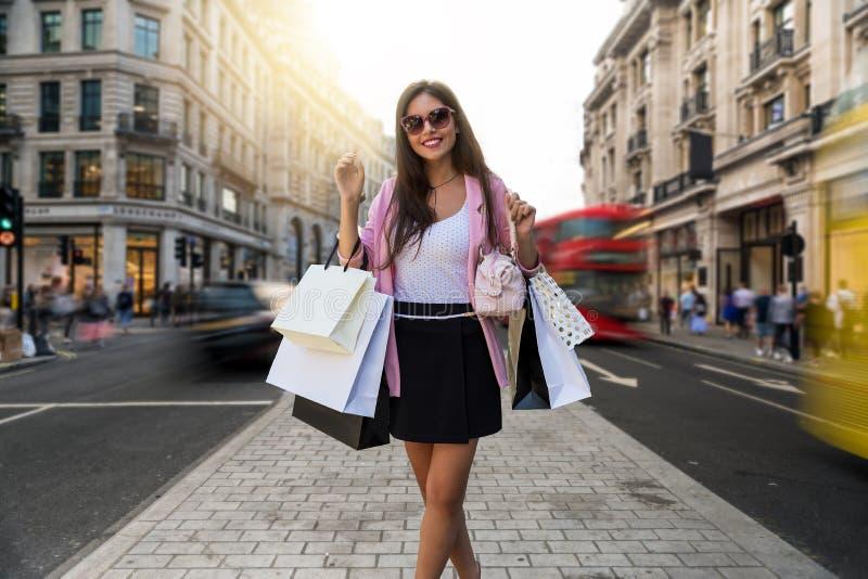 Stadskvinnan med många hänger löst i hennes hand går att shoppa på Regent Street i London arkivfoton