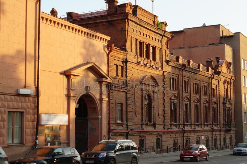 Stadslandskap: Gata för 22 Pervomaiskaya, byggnaden av röd tegelsten på solnedgången Skola av musik arkivbilder