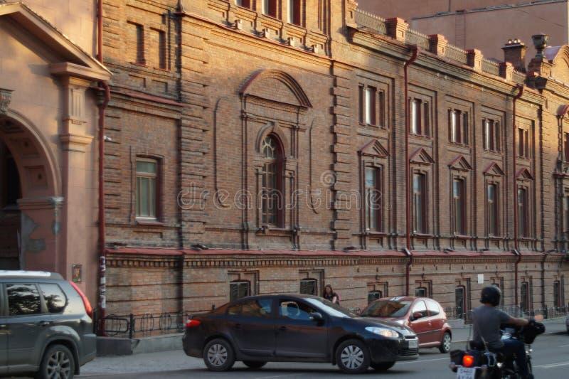Stadslandskap: Gata för 22 Pervomaiskaya, byggnaden av röd tegelsten på solnedgången Skola av musik royaltyfri foto