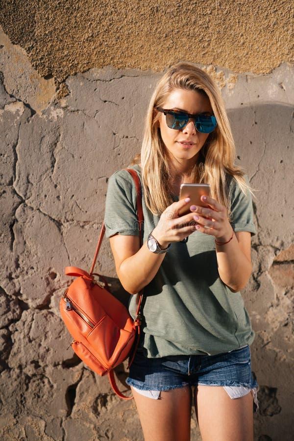 Stadslevensstijl, hipster meisje die een telefoon met behulp van die op smartphone app in een straat texting stock fotografie