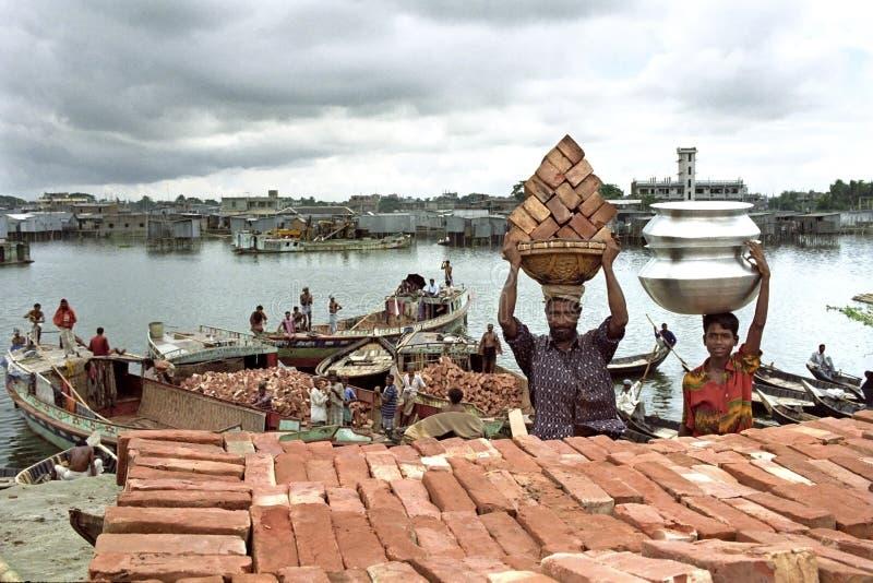 Stadsliv i Dhaka med arbetare, slumkvarteret och floden trafikerar arkivfoto