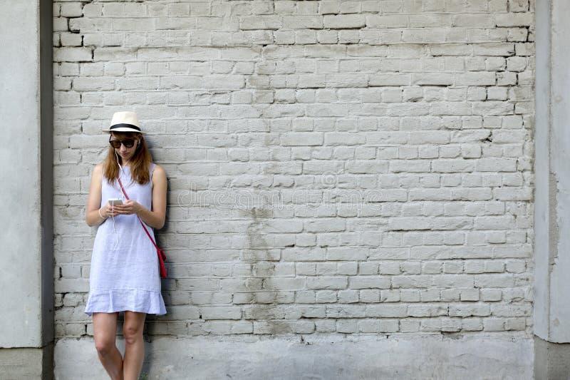 Stadslivbegrepp Anseende för ung kvinna bredvid den vita tegelstenväggen som lyssnar till musik i hörlurar royaltyfri bild