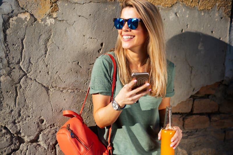 Stadslivsstil, hipsterflicka som anv?nder en telefon som smsar p? smartphoneappen i en gata fotografering för bildbyråer