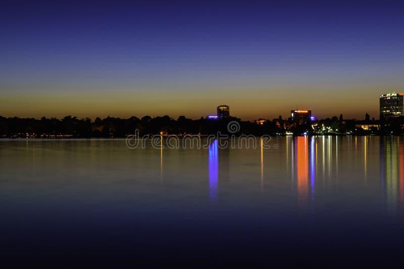Stadsljus som reflekterar på natten över vattnet av Herastrau sjön arkivbilder