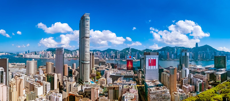 Stadsmening van Kowloon-schiereiland en Hong Kong-eiland bij hete middag stock afbeeldingen