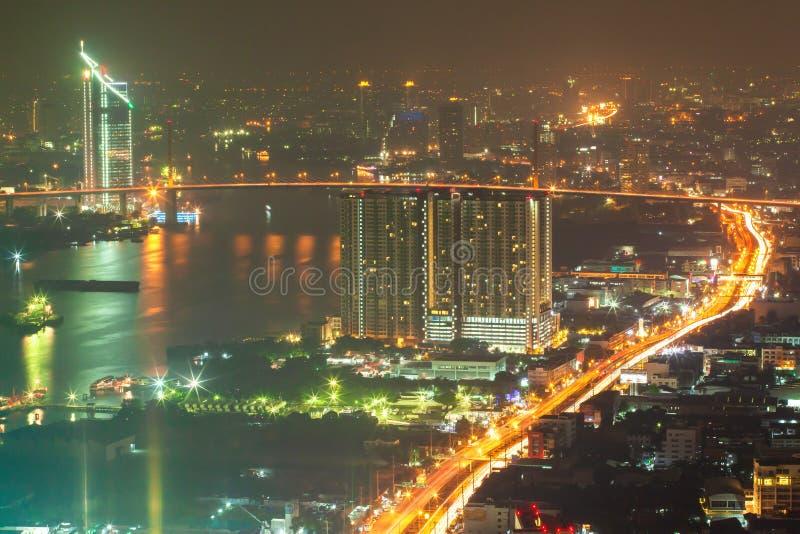 Stadsnacht door rivieroever, panoramisch satellietbeeld van gebouwen de van de binnenstad van Bangkok en Chao Phraya River bij na stock afbeelding