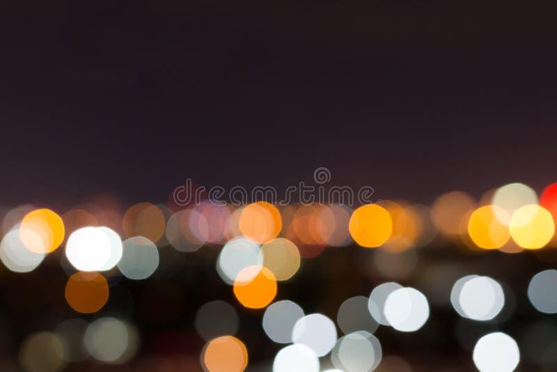 Stadsnatt med mörk himmel, abstrakt suddighetsbokehljus royaltyfri fotografi