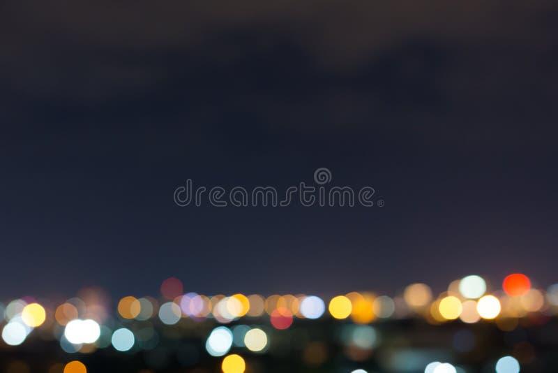 Stadsnatt med mörk himmel, abstrakt suddighetsbokehljus arkivbild