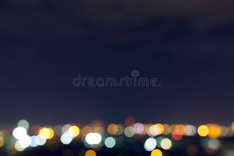 Stadsnatt med mörk himmel, abstrakt suddighetsbokehljus arkivfoto
