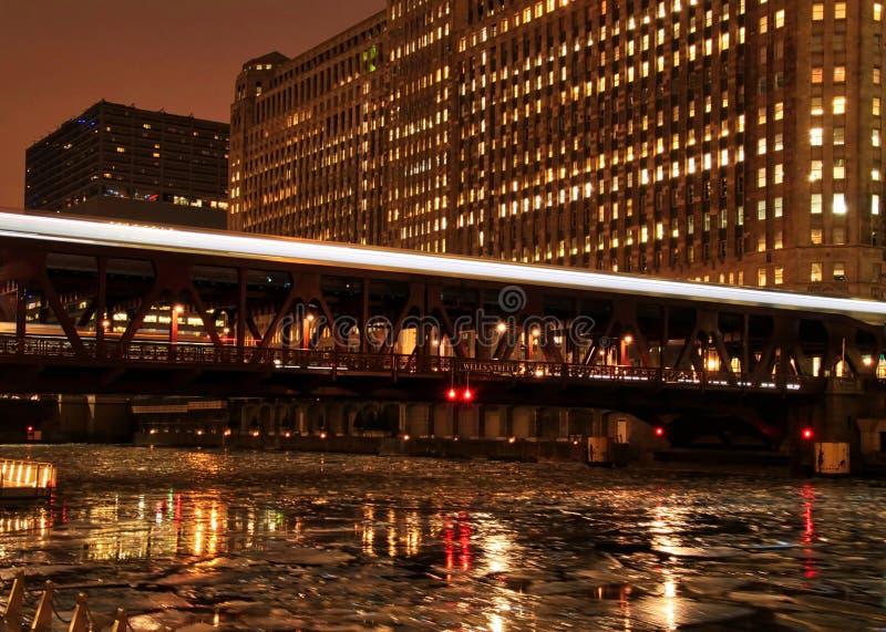 Stadsnattljus är upplysta från den Chicago bron och det rörande el-drevet som rusar över det arkivbild
