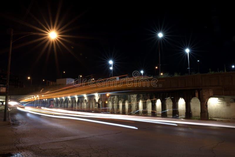 Stadsnatttrafik som kommer ut ur en viaduc för järnvägbrotunnel fotografering för bildbyråer