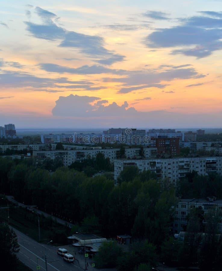 Stadspanorama på bakgrunden av solnedgånghimmel och moln arkivfoton