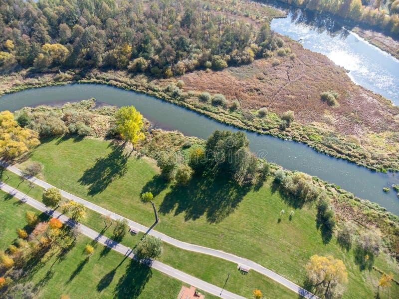 Stadspark met dichtbegroeide herfstbomen, groene gazons, bikeway en rivier royalty-vrije stock fotografie