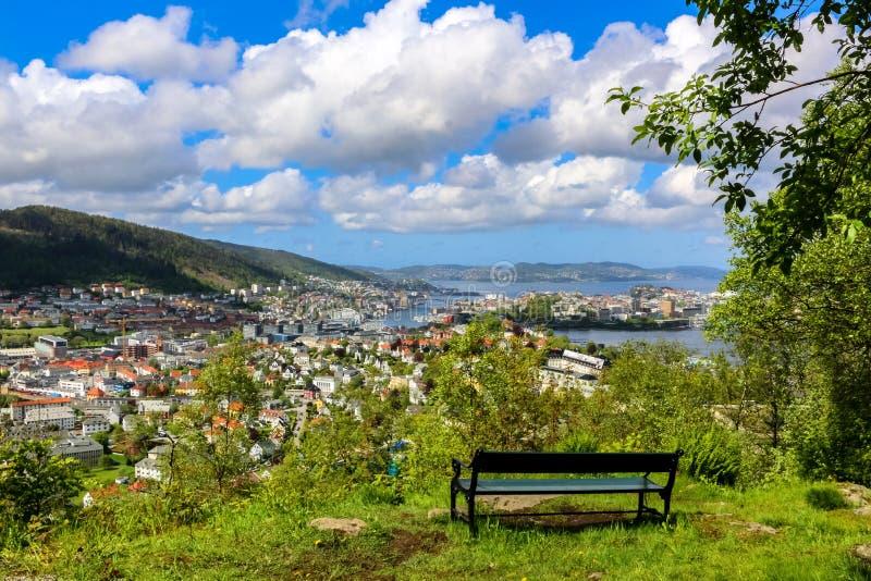 Stadsplats med en tom bänk på grönt gräs, överblick av Bergen Center och spridda vita moln i solljuset royaltyfri foto