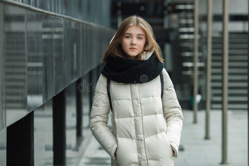 Stadsportret van het jonge mooie blonde modieuze meisje stellen in de lentedaling in openlucht van witte laag zwarte gebreide sja stock afbeeldingen