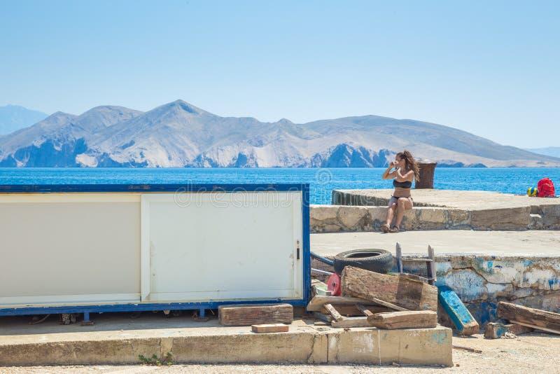 StadsPula, Kroatienrepublick Kvinna som solbadar vid havskusten Kullar och sol 30 Juli 2016 royaltyfri fotografi