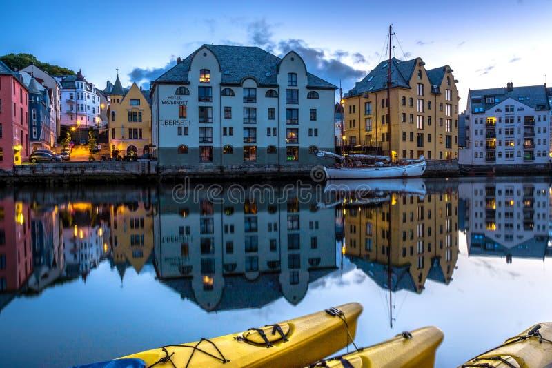 Stadsscène met Huizen en Boten in een Kalm Kanaal bij Nacht in Alesund worden weerspiegeld die stock foto