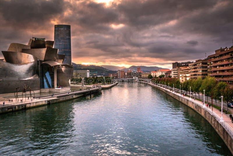 Stadsscène met Weergeven van Nervion-Rivier en het Guggenheim-Museum Bilbao bij Dramatische Zonsondergang royalty-vrije stock afbeeldingen