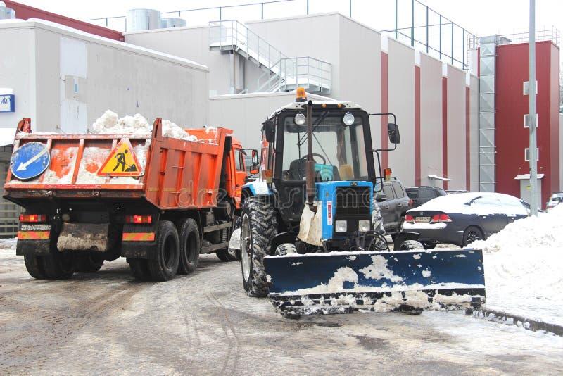 Stadsservice snöar special utrustning för borttagning efter snöfall stads- hjälpmedel Traktoren laddar snö in i lastbilen royaltyfria foton