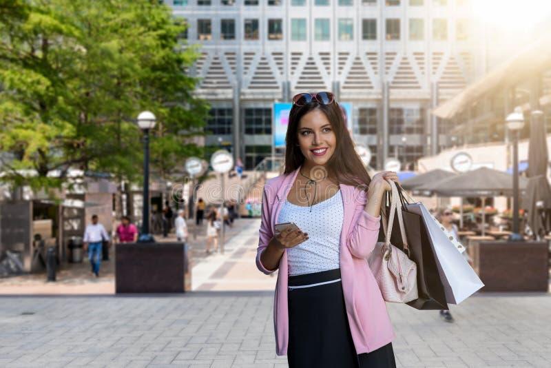 Stadsshoppingflicka med shoppingpåsar och mobiltelefon i hennes hand i Canary Wharf, London arkivfoton