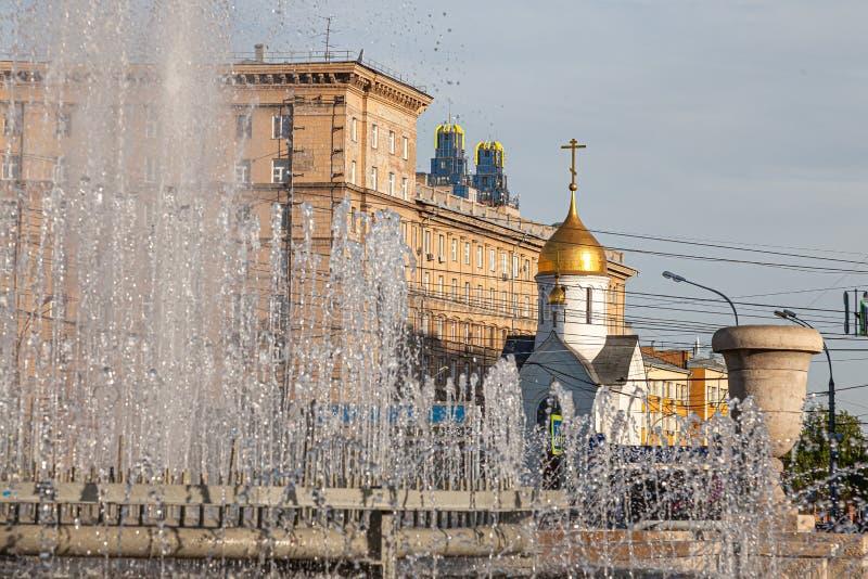 Stadsspringbrunn med färgstänk och strålar av vatten mot bakgrunden av byggnader och enfärgad kyrklig kupol med ett kors arkivfoton