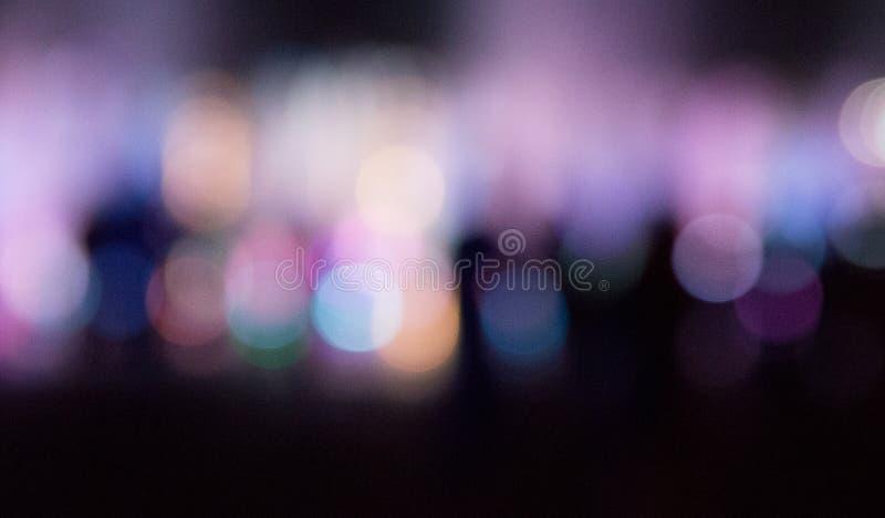 Stadsspringbrunnen med färgbelysning på natten ut ur fokus fotografering för bildbyråer