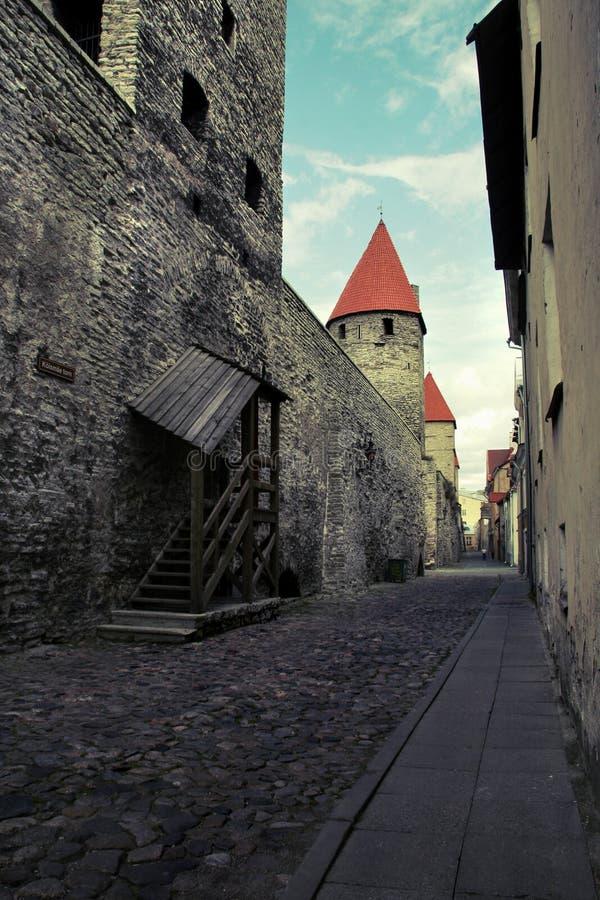 Stadsstraat van de oude stad in Tallinn met een oude muur van kalksteen en rode tegeldaken op de torens stock fotografie