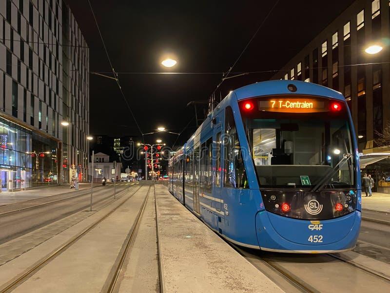 Stadsstraatbeeld van een blauwe SL-tram met incidentele mensen op de achtergrond in Stockholm stock fotografie