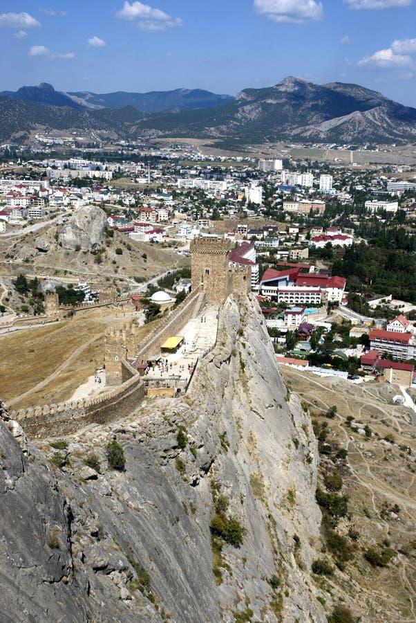 Stadt mit einer Festung unter Bergen stockbild