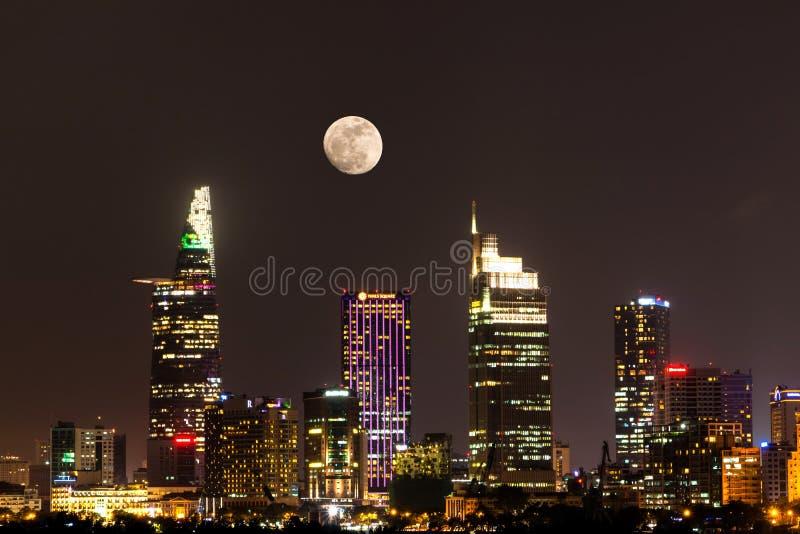 Stadt-Szene mit dem Mond, der über Ho Chi Minh Stadt zentrales Geschäftsgebiet um Nacht sich erhöht stockbild