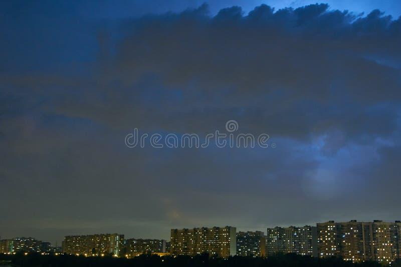 Stadtbild an der Dämmerung mit Gewitter über Wohnanlagen stockbild