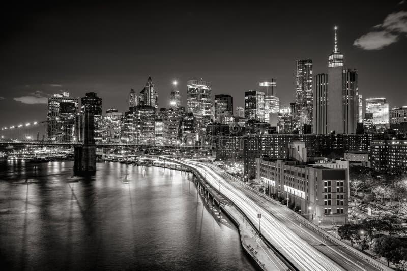 Stadtbild nachts des Lower Manhattan-Finanzbezirkes mit belichteten Wolkenkratzern New- York Cityschwarzes u. -WEISS lizenzfreie stockfotos