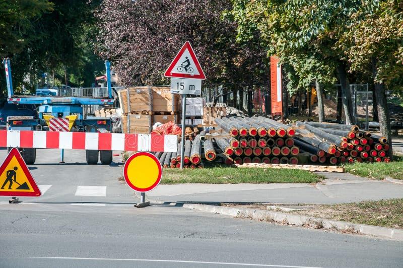 StadtFernheizungsrohrleitungswiedergutmachung und -rekonstruktion parallel zur Straße mit Baumaschinen und Sicherheitsstraße lizenzfreie stockbilder