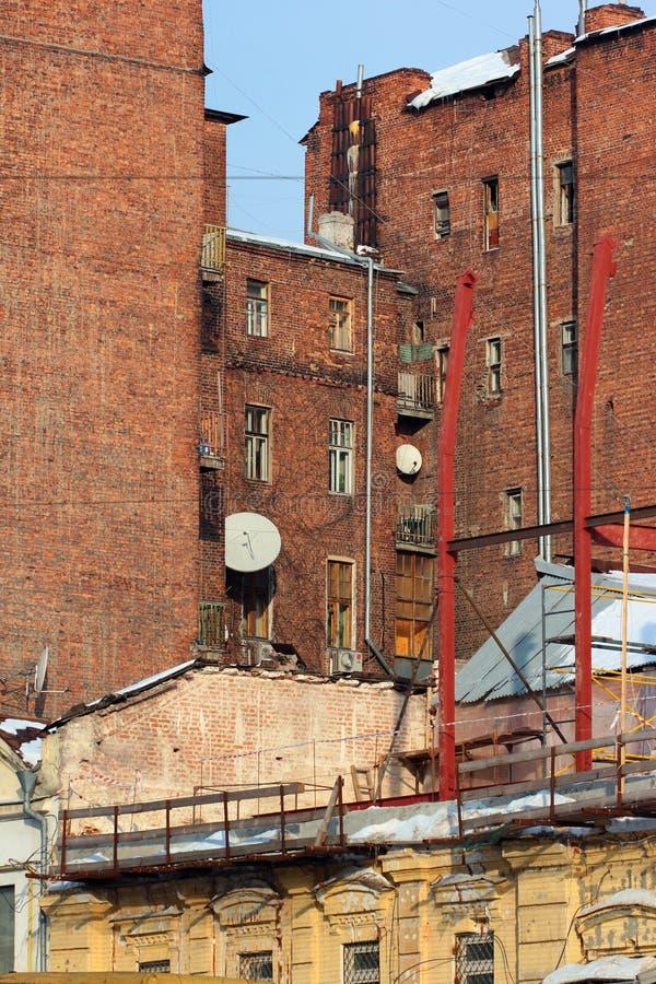 Stadthintergrund, alte Wände des roten Backsteins des inneren Hinterhofes stockfotografie